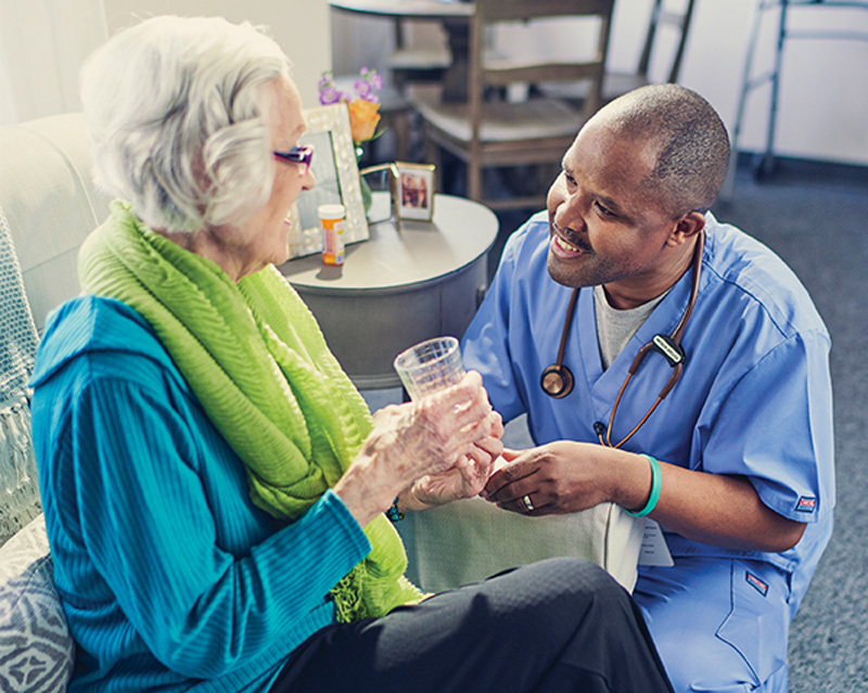 Healthcare provider speaking with an elderly patient
