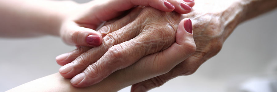 Holding an elderly hospice patient's hand